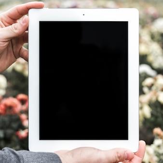 屋外でデジタルタブレットを持っている人の手のクローズアップ