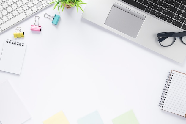 Скрепки; клавиатура; ноутбук; спиральный блокнот и заметки на белом столе с пространством для написания текста