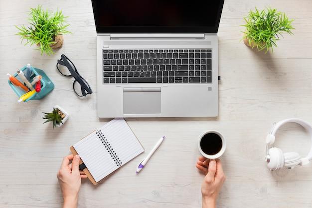 ノートパソコンを開くと木製の机の上の日記とコーヒーカップを持つ人