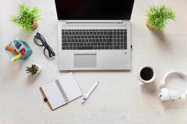 ラップトップ付き事務用品。木製の机の上のヘッドフォンとコーヒーカップ