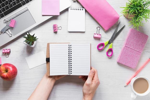 木製の机の上のオフィス文房具とスパイラルメモ帳を持っている人の手のクローズアップ
