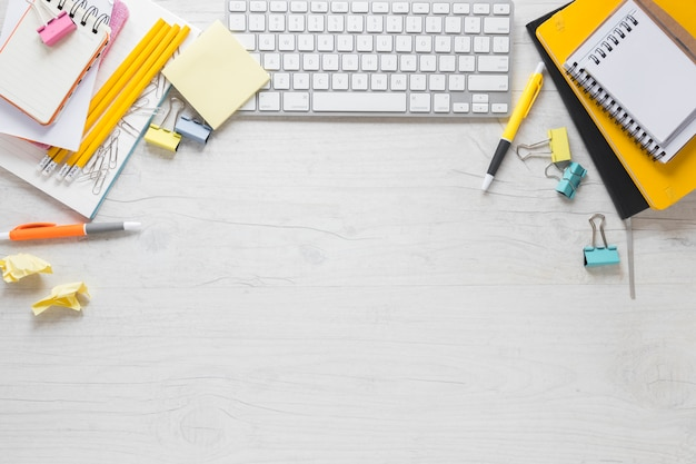 Поднятый вид офисных канцелярских принадлежностей с клавиатурой и копией пространства для написания текста на деревянный стол