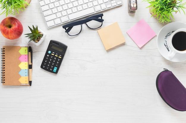 木製の机の上の電卓と事務用品とアップル