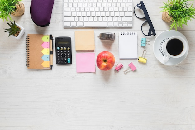白い木製の机の上のオフィス文房具とアップルとコーヒーカップのトップビュー