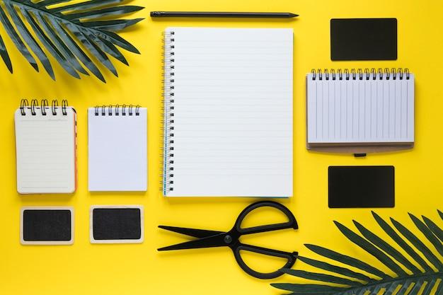 はさみ;カード;と黄色の背景にスパイラルメモ帳の種類と鉛筆
