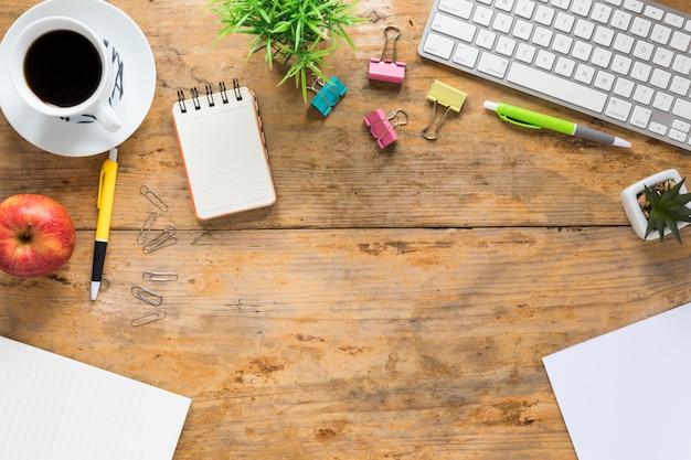 コーヒーカップの上から見た図。木製の机の上のリンゴとオフィスの文房具