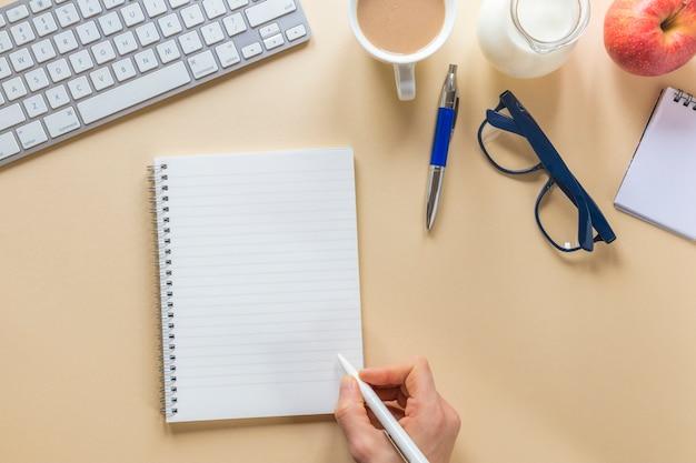 ベージュのオフィスの机の上にペンでスパイラルメモ帳に書く人の手のクローズアップ