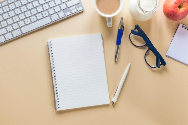 ティーカップミルクとアップルキーボードとベージュ色の背景上の文房具