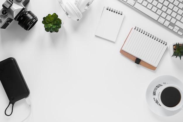 Камера; внешний аккумулятор; кактус растение; дневник; чашка чая и клавиатура на белом столе