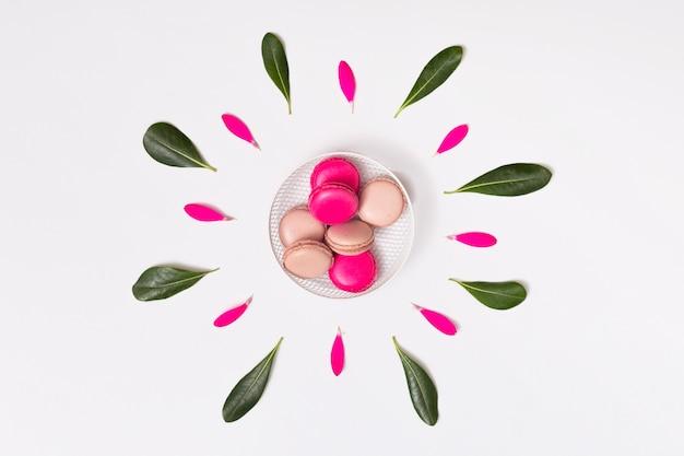 花びらと葉の間の皿の上のマカロン