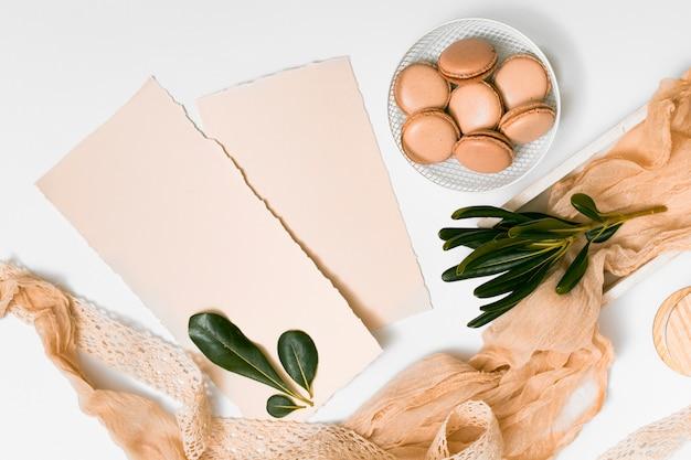 Набор бумаги и миндальное печенье на тарелке возле текстильных и веток растений
