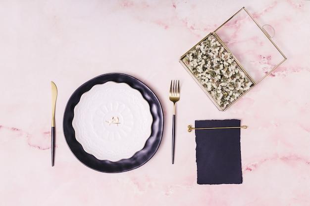 Набор цветов в коробке и бумаге возле тарелки и столовых приборов