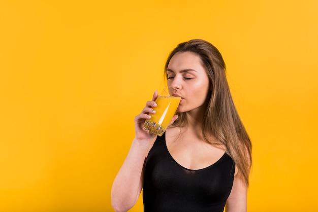 魅力的な若い女性はガラスからジュースを飲む