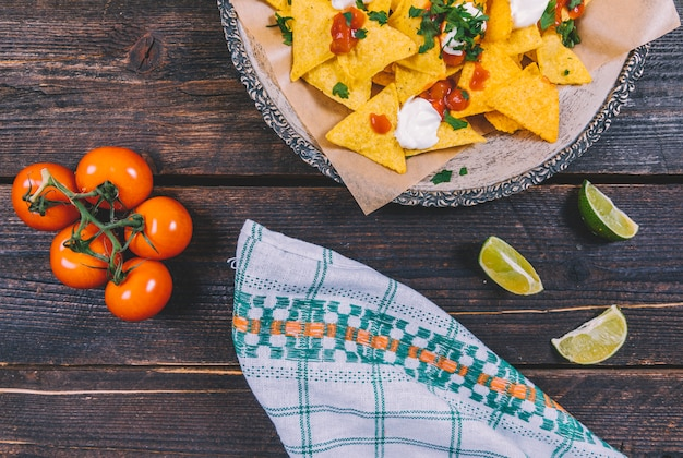 茶色の木製の机の上のレモンスライスとチェリートマトのプレートで飾られたおいしいメキシコのナチョス