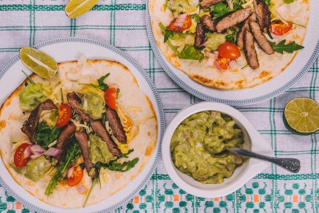 テーブルクロスの上のワカモレとトルティーヤの野菜とメキシコのビーフストライプ