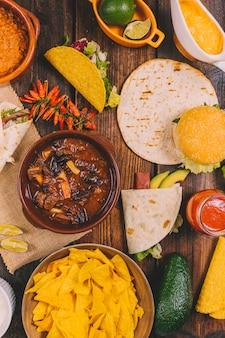 ビーフシチュー;トルティーヤ;おいしいメキシコのナチョス。赤唐辛子;ハンバーガーとアボカドの茶色のテーブル