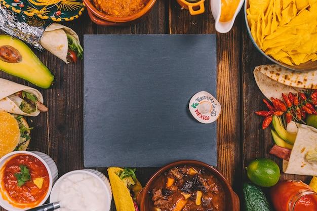 茶色のテーブルに様々なおいしいメキシコ料理に囲まれた黒いスレート