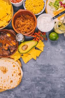 コンクリートの背景上のおいしいメキシコ料理の様々な