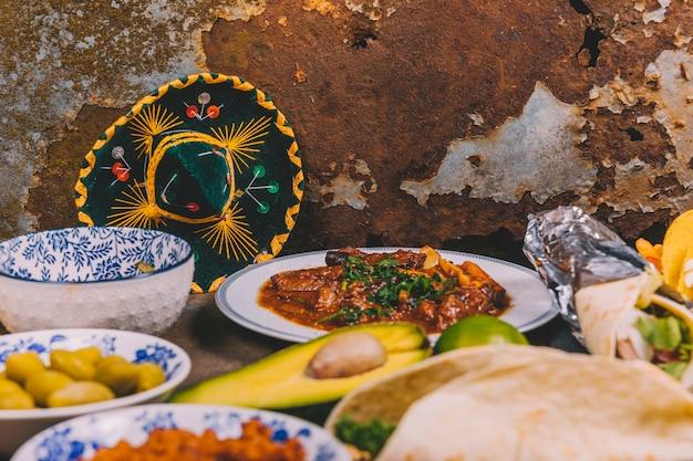 メキシコの帽子とさびた背景上のさまざまなおいしいメキシコ料理