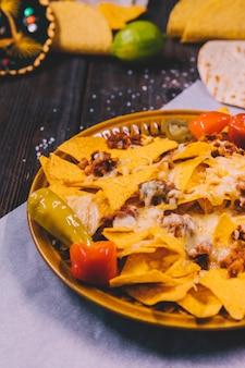 バター紙の上の皿に黄色のメキシコのナチョスのクローズアップ