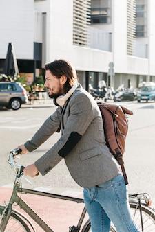 彼の自転車と道路上に立っているバックパックを運ぶ男の側面図
