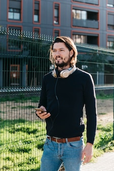 フェンスの近くに立っている彼の首の周りのヘッドフォンに接続されている携帯電話を持つハンサムな若い男性