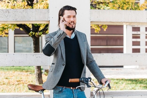 Улыбающийся молодой человек разговаривает по мобильному телефону, стоя с велосипедом в парке