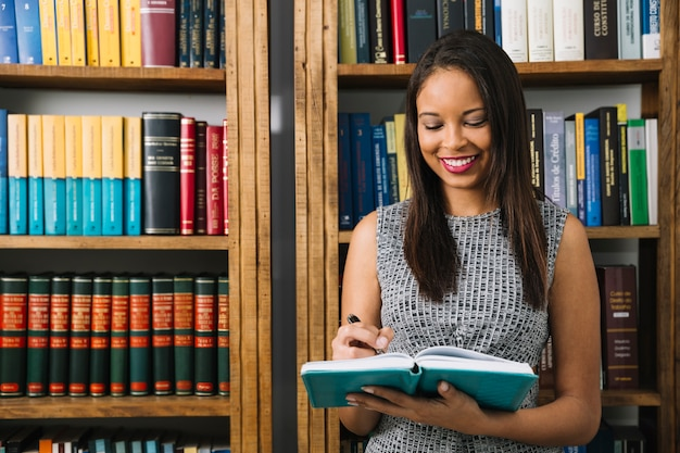 本を持つアフリカ系アメリカ人の若い女性の笑みを浮かべてください。
