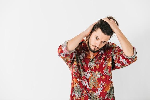 白い背景で隔離の手で彼の髪をグルーミングする男の肖像