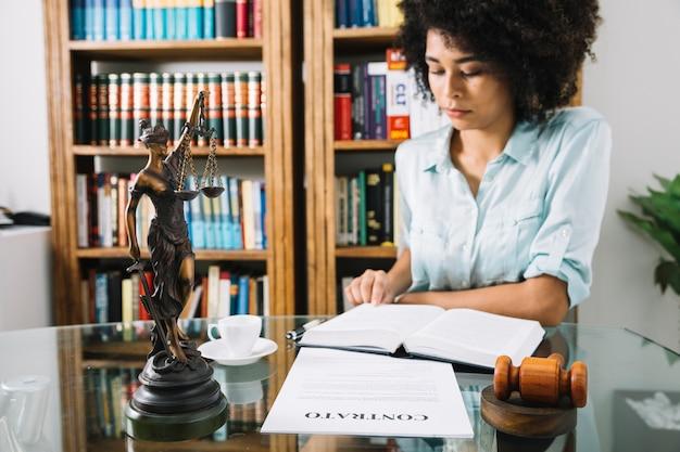 カップとドキュメントのテーブルで本を持つアフリカ系アメリカ人の若い女性