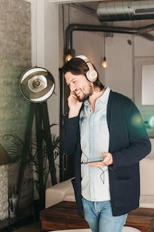携帯電話に接続されているヘッドフォンで音楽を楽しんでいる笑みを浮かべて男