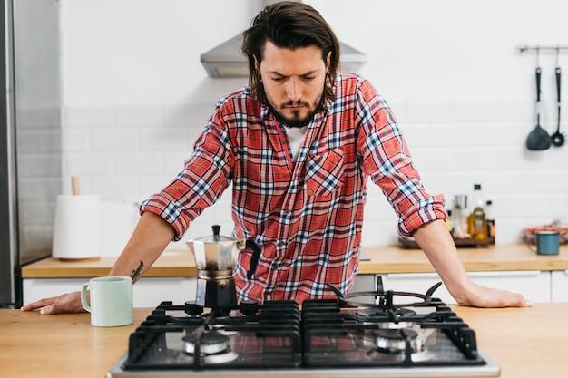 深刻な若い男が台所でコーヒーを準備します。