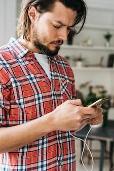 携帯電話でハンサムな若い男のテキストメッセージ