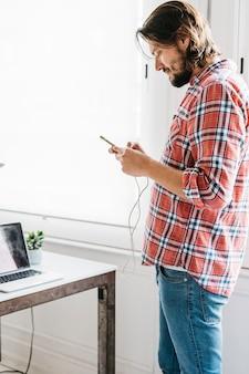 テキストメッセージの携帯電話を使用してスタイリッシュな若い男
