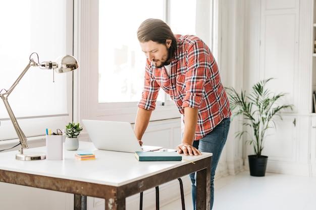 Мужчина стоит возле стола и смотрит на ноутбук