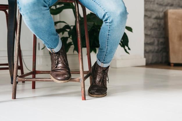スツールに座っている茶色の靴でエレガントなスタイリッシュな男の低いセクション
