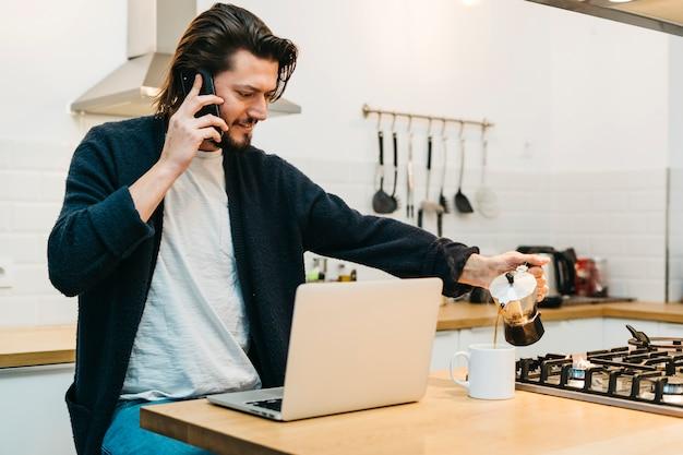 ハンサムな若い男が台所のカウンターにラップトップで携帯電話で話しているマグカップでコーヒーを注ぐ