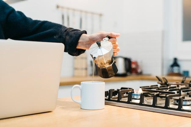 ガスコンロの近く白いマグカップでコーヒーを注ぐ人の手のクローズアップ