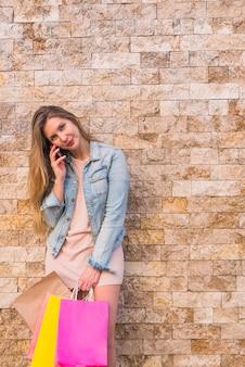 電話で話している買い物袋を持つ若い女