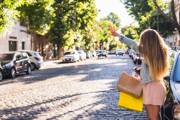 タクシーをキャッチする買い物袋を持つ女性