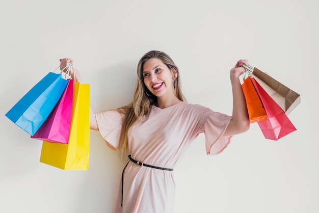 買い物袋で立っている幸せな女