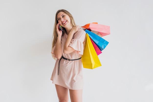 Счастливая женщина с хозяйственными сумками разговаривает по телефону