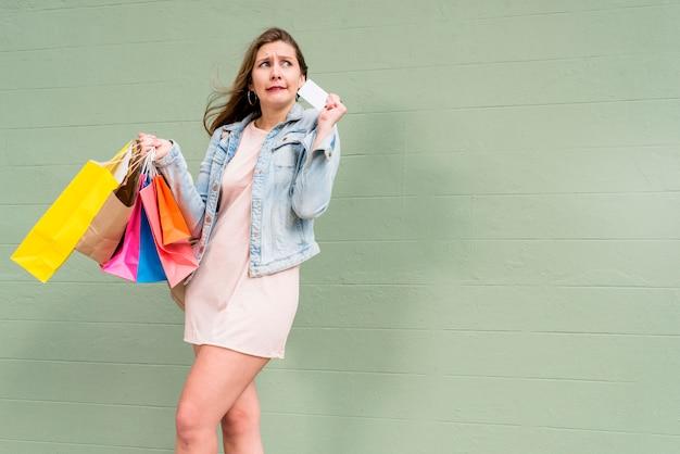 クレジットカードと買い物袋の緑の壁に立っている女性