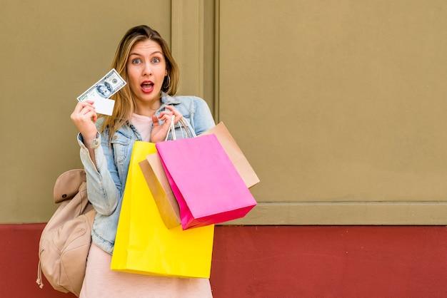 Изумленная женщина стоя с хозяйственными сумками и деньгами