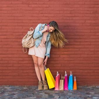レンガの壁に電話で話している買い物袋を持つ女性