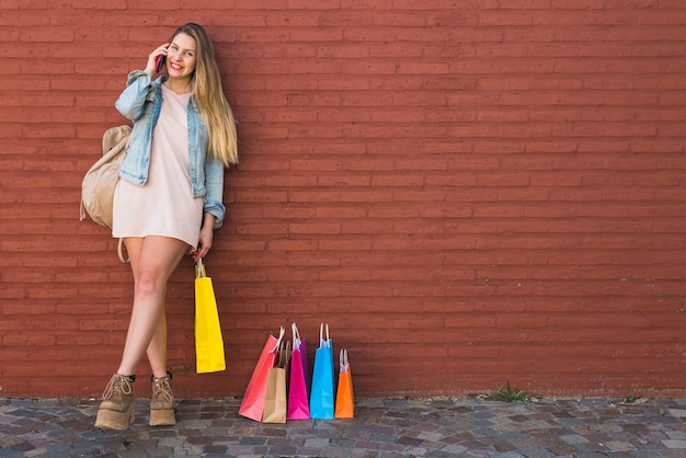 電話で話している買い物袋の近くの幸せな女