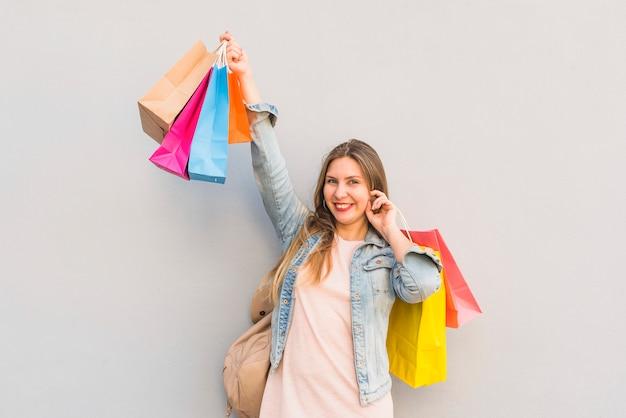 うれしそうな女性の明るい壁で明るい買い物袋に立っています。