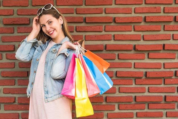 レンガの壁に背中の後ろに明るい買い物袋で立っている女性