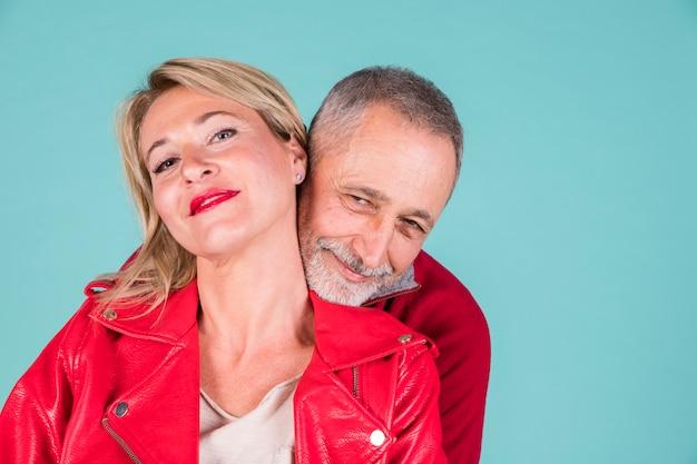 ターコイズブルーの背景に対して成熟したカップルを笑顔の愛情のある肖像画
