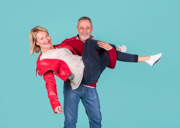 ターコイズブルーの背景に対して彼の妻を運ぶ成熟した女性の肖像画を笑顔